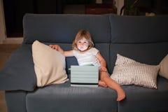 Kindzitting in bank met tablet het kijken Royalty-vrije Stock Afbeeldingen