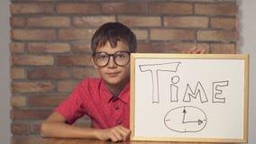 Kindzitting bij de bureauholding flipchart met het van letters voorzien tijd op de rode bakstenen muur als achtergrond stock video