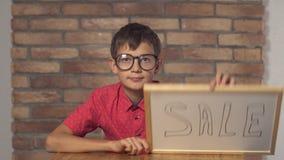 Kindzitting bij de bureauholding flipchart met het van letters voorzien verkoop op de rode bakstenen muur als achtergrond stock videobeelden