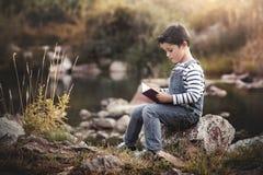 Kindzitting die een boek lezen stock foto