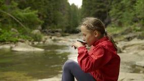 Kindzitting op de bank van de bergrivier stock video
