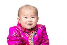 Kines behandla som ett barn leende med den traditionella dräkten Arkivbilder