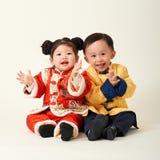 Kines behandla som ett barn pojken och flickan i dräkt för nytt år för traditionell kines arkivfoto