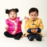 Kines behandla som ett barn pojken och flickan i dräkt för nytt år för traditionell kines arkivbild