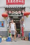 Kines shoppar ägaren framme av hans lager, Peking, Kina Arkivfoto