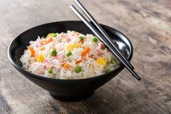 Kines stekte ris med grönsaker och omelett i svart bunke på trä fotografering för bildbyråer