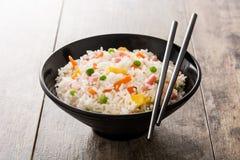Kines stekte ris med grönsaker och omelett i svart bunke på trä arkivbilder