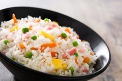 Kines stekte ris med grönsaker och omelett i svart bunke på trä royaltyfri bild
