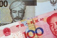 Kines 100 Yuan Bank Note With 2000 sedel för indonesisk Rupiah arkivfoton