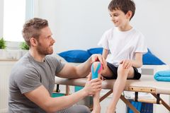 Kinesio taping after knee injury. Little patient with kinesio taping after knee injury Royalty Free Stock Photos