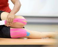 Kinesio tapping on knee joint. Tapping on qaudricep muscle for support patella and control knee joint pain royalty free stock images