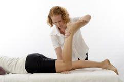 Kinesiologist, der Kniebeugemuskeln behandelt Lizenzfreie Stockfotografie