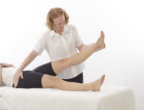 Kinesiologist treating leg Royalty Free Stock Images