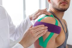 Free Kinesiology Taping. Physical Therapist Applying Kinesiology Tape To Patient Shoulder. Female Therapist Treating Injured Stock Image - 182433781