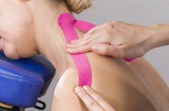 Kinesiotaping Körperlicher Therapeut, der Band am geduldigen cervi anbringt Lizenzfreies Stockfoto