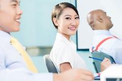 Kinesisk affärskvinna i mötet som ser kameran Arkivfoton