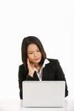 Kinesisk affärskvinna som fungerar på Lapto Arkivbild
