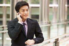 Kinesisk affärsman utanför kontor på den mobila telefonen Arkivbild