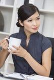 Kinesisk asiatisk kvinnaaffärskvinna Drinking Tea eller kaffe fotografering för bildbyråer
