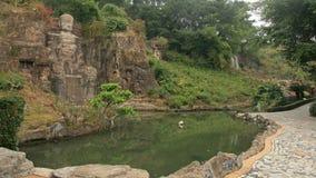 Kinesisk Buddhastenstaty nära dammet Arkivfoto
