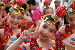 Kinesisk dansare i traditionell dräkt på den internationella folklorefestivalen för barn och guld- fisk för ungdom royaltyfria bilder