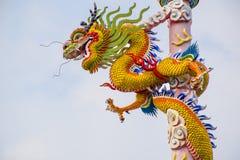 Kinesisk drake vriden spole på högväxta pelare På blåttskyen arkivbilder
