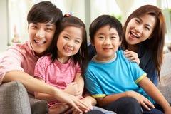 Kinesisk familj som hemma kopplar av på sofaen Arkivfoton