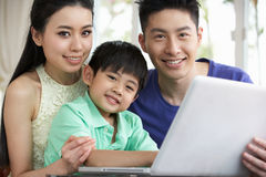 Kinesisk familj som sitter genom att använda bärbar dator hemma Royaltyfria Foton