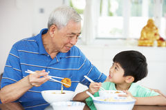 Kinesisk farfar och sonson som äter mål Arkivbild