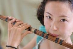 Kinesisk flicka som blåser bambuflöjten Arkivbild