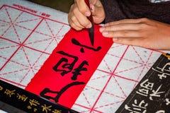 Kinesisk flicka som gör kalligrafiövning Arkivbilder