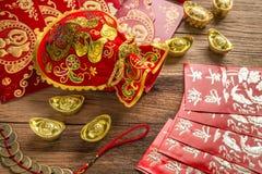 Kinesisk garnering för nytt år, kinesisk röd påse och guld- guldtacka Royaltyfria Bilder