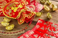 Kinesisk garnering för nytt år, kinesisk röd påse och guld- guldtacka Royaltyfri Foto