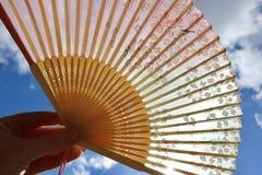Kinesisk handfan med himmel och solsken i bakgrund Rymt av handen royaltyfri bild