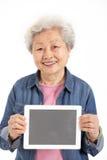 Kinesisk hög kvinna som rymmer den Digital tableten Royaltyfri Fotografi