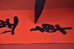 Kinesisk kalligrafi, characterÂs översättning är medlet Arkivfoto