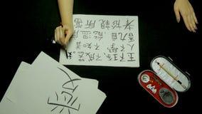 Kinesisk kalligrafi för kvinnlig handhandstil genom att använda borsten och färgpulver på rispapper Slut som rymmer upp föreståen Arkivfoton