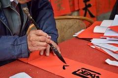 Kinesisk kalligrafi som är skriftlig vid en gamal man En teckenöversättning är cirkeln Arkivfoto