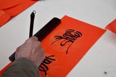 Kinesisk kalligrafi som är skriftlig vid en gamal man En teckenöversättning är livslängden Arkivbild