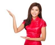 Kinesisk kvinna med cheongsam med presentation för två hand royaltyfri bild