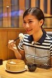 Kinesisk kvinna som äter den ångade klimpen i restaurang arkivbild