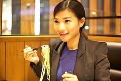 Kinesisk kvinna som äter nudlar i restaurang royaltyfria bilder