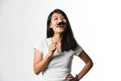Kinesisk kvinna som har gyckel med en fejkamustasch arkivbild