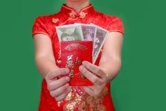 Kinesisk kvinna som rymmer det röda kuvertet för nytt år eller den hong baoen Royaltyfri Foto