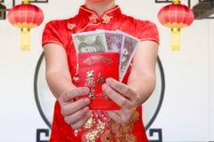 Kinesisk kvinna som rymmer det röda kuvertet för nytt år eller den hong baoen Royaltyfri Fotografi