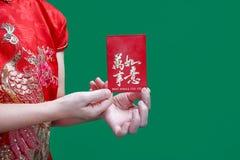 Kinesisk kvinna som rymmer det röda kuvertet för nytt år eller den hong baoen Fotografering för Bildbyråer