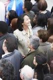 Kinesisk kvinna som vänder mot den annan riktningen från den multietniska folkmassan Arkivfoton