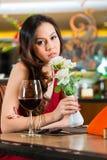Kinesisk kvinna som väntar i restaurangen för datum arkivbild