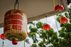 Kinesisk lykta- och wind‐ sätter en klocka på på den kinesiska templet Arkivfoto