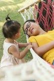 Kinesisk mamma som ligger p? h?llande ?gonen p? dotter f?r h?ngmatta arkivbild